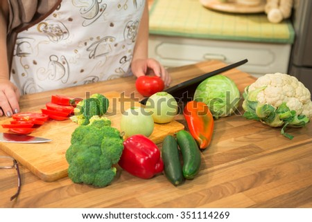 Unrecognizable woman following recipe on touchpad and preparing food in the kitchen. - stock photo
