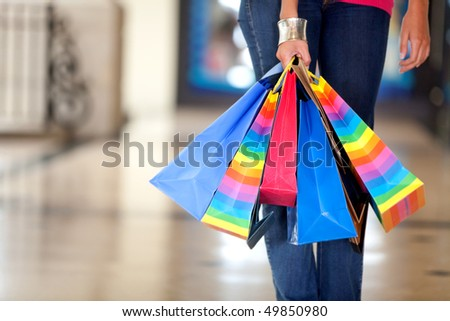 Unrecognizable woman holding bags in a shopping center - stock photo
