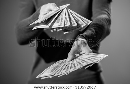 Unrecognizable woman holding many dollar's banknotes, monochrome image - stock photo