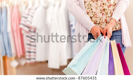 Unrecognizable woman in a store holding shopping bags