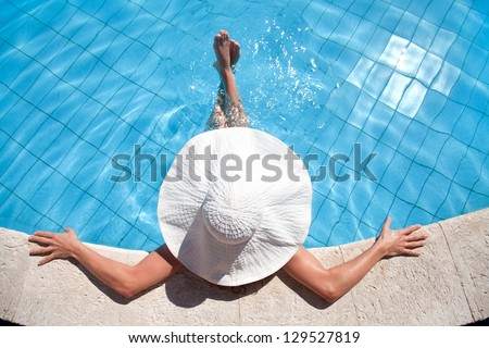 Unrecognizable woman in big hat relaxing on the swimming pool - stock photo