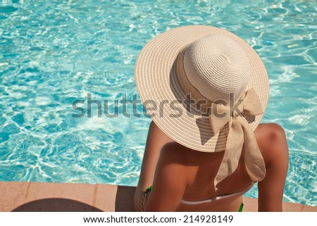 Unrecognizable woman in elegant big hat relaxing on the swimming pool. Enjoying summer sun and tanning - stock photo