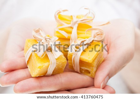 Unrecognizable woman's hands holding pieces of natural beeswax, packed and decorated - stock photo