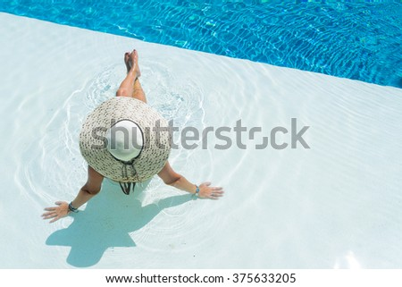 Unrecognizable woman wearing a big hat relaxing at the swimming pool - stock photo