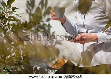 unrecognizable young business woman using her smartphone outdoors and relaxing.focus in the hand - stock photo