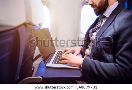 Unrecognizable young businessman with notebook sitting inside an airplane - stock photo
