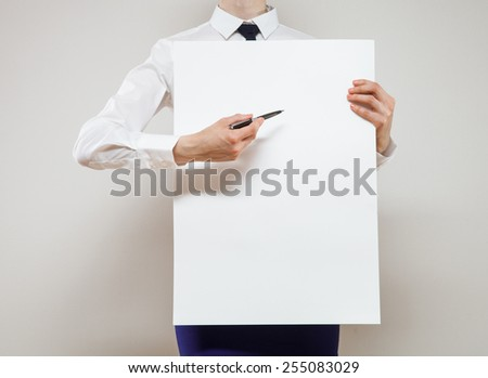 Unrecognizable young businesswoman holding a white poster on neutral background - stock photo