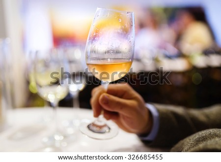 Unrecognizable young man enjoying a drink in a wine bar - stock photo