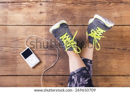 Unrecognizable young runner sitting on a floor. Studio shot on wooden background. - stock photo