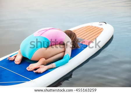Unrecognizable young woman doing yoga on sup board with paddle. Meditative pose, back view - concept of harmony with the nature, free and healthy living, freelance, remote business. - stock photo