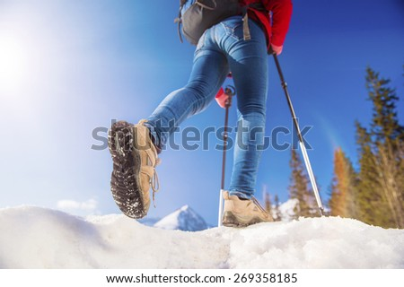 Unrecognizable young woman hiking outside in sunny winter mountains - stock photo