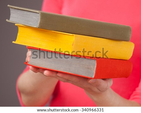 Unrecognizable young woman holding three books, gray background