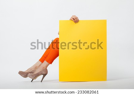 Unrecognizable young woman in orange pants holding blank yellow paper sitting on the floor - stock photo