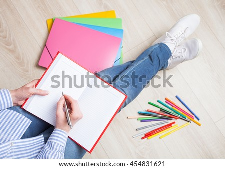 Unrecognizable young woman writing something in a diary sitting on the floor in a relaxed pose - stock photo
