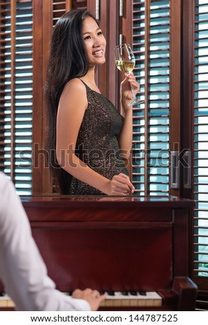 Unrecognized pianist playing for a beautiful lady with a glass of white wine - stock photo