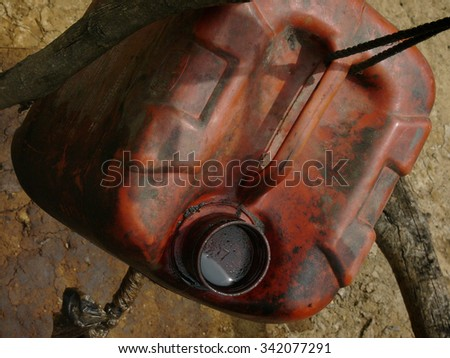 Unrefined crude oil is collected in a jerry can amid contaminated land at a heavily polluted, illegal oil field in Kadewan, East Java, Indonesia. - stock photo