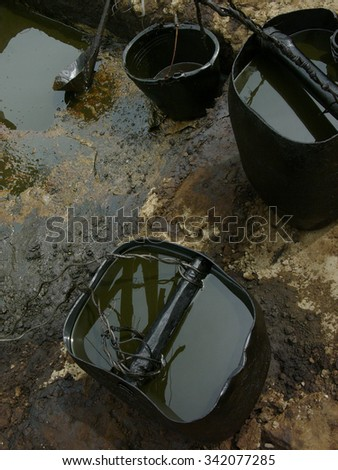 Unrefined crude oil is collected in oil drums amid contaminated soil and water at a heavily polluted, illegal oil field in Kadewan, East Java, Indonesia. - stock photo