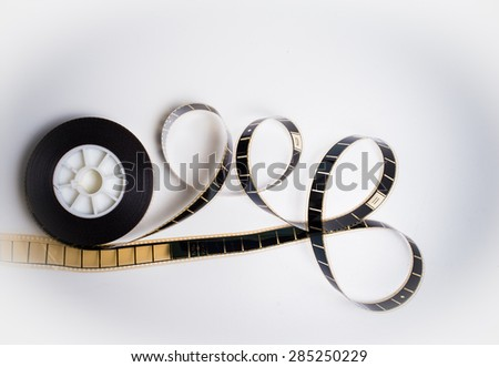 Unrolled 35 mm movie film on white background vintage color effect - stock photo