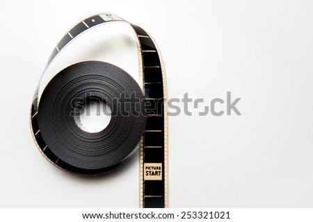 Unrolled 35mm movie reel with picture start frame in vertical position, vintage color effect on white background - stock photo