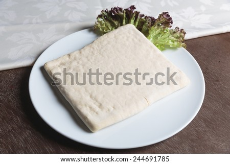 Unrolling dough on plate with salad on plate - stock photo