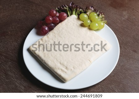 Unrolling dough with grape and salad on plate - stock photo
