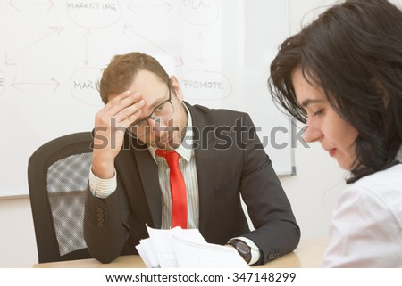 Unsatisfied boss and sad female worker  - stock photo