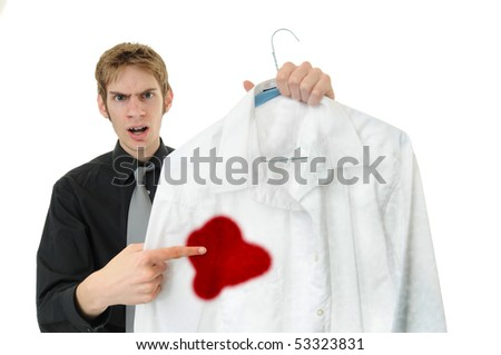 Unsatisfied customer holds up a dry cleaned suit. Missed a spot! - stock photo