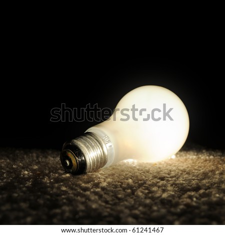 Unscrewed illuminated light bulb on the floor, brightly lit in the darkness. Black background copyspace above. - stock photo