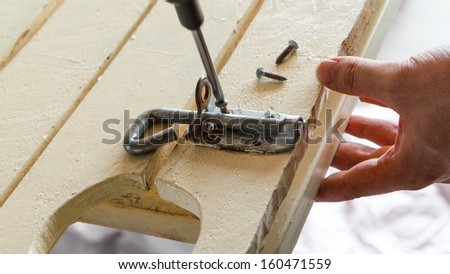Unscrewing Bolt.  Man holding a wooden gate while he unscrews the rusty screws from a lock bolt.  Screwdriver is turning.