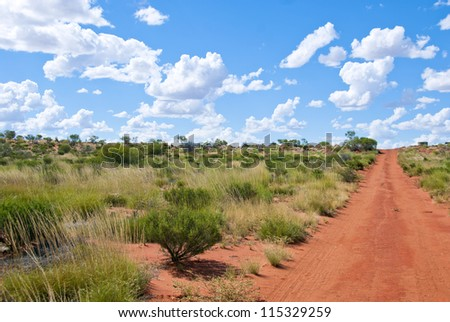 Unsealed dirt road with typical red sand leading through the outback of the red center of Australia - stock photo