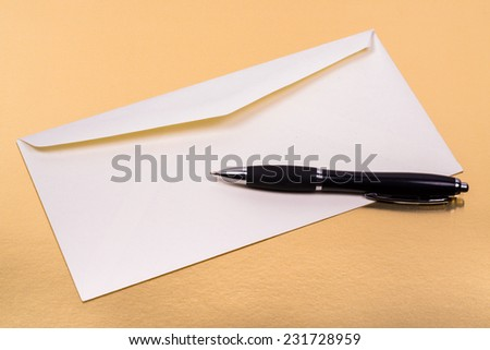 unsealed white envelope with a ballpoint pen on the side on a gold background - stock photo