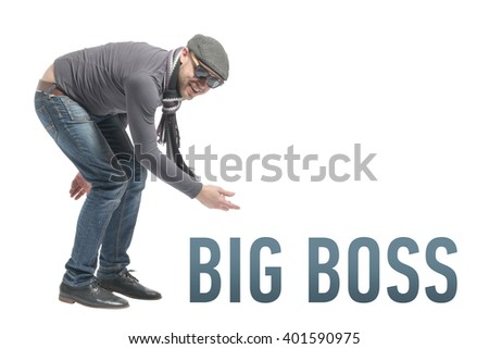 Unshaven bald man wearing a cap, jeans, sunglasses and scarf crouched and points to the inscription BIG BOSS. Isolated - stock photo