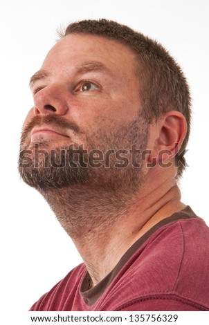 Unshaven Caucasian male facing up and camera left - stock photo