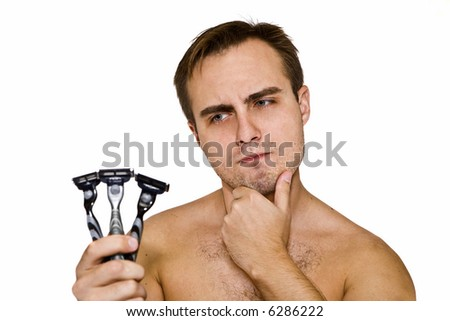 Unshaven guy with three razors - stock photo