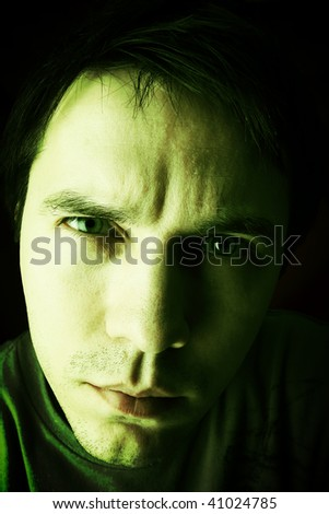Unshaven man in casual wear posing in the studio. Dark background. Aggressive and attentive. Green tint.