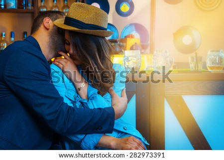 unshaven man says girlfriend's ear, and she laughs at the bar. horizontal photo - stock photo