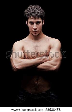 unshaven young man against dark background - stock photo