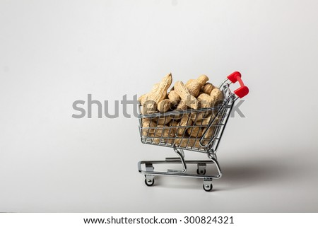 unshelled peanuts in the supermarket trolley, isolated on white background - stock photo