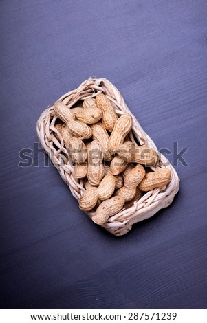 unshelled peanuts peanuts isolated in basket on dark background - stock photo