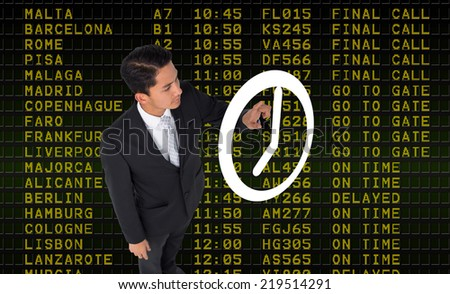 Unsmiling asian businessman pointing to a white clock against black airport departures board - stock photo