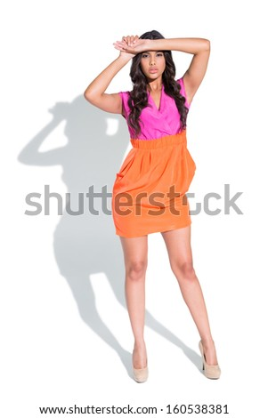 Unsmiling attractive brunette posing and touching her forehead on white background - stock photo