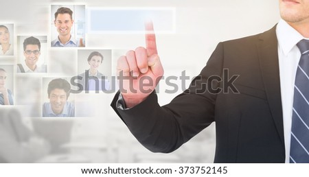 Unsmiling businessman pointing his finger against grey background