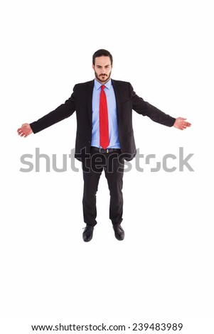 Unsmiling businessman standing with arms outstretched on white background - stock photo