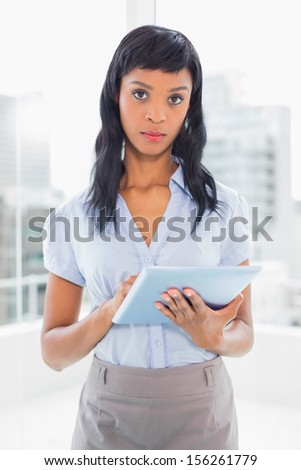 Unsmiling businesswoman using a tablet pc in office - stock photo