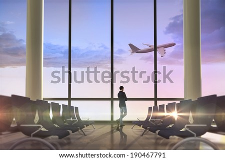 Unsmiling casual businessman with arms crossed against airplane flying past departures lounge