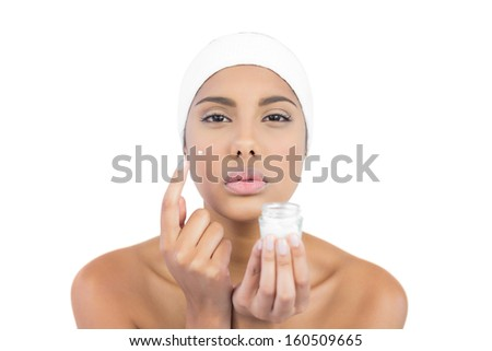 Unsmiling nude brunette using moisturizer looking at camera on white background