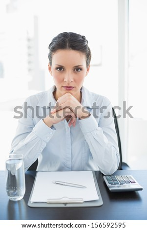 Unsmiling stylish brunette businesswoman joining her hands and looking at camera in bright office