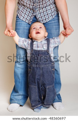 Unsure baby looking at his mother before making first steps - stock photo