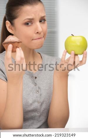 Unsure bewildered girl choosing apple or cake. beautiful young woman choosing between apple and cupcake - stock photo