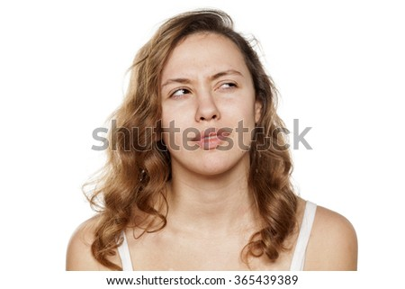 unsure pensive young woman without make-up - stock photo